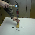Insert screwdriver into pin by tapping with hammer.